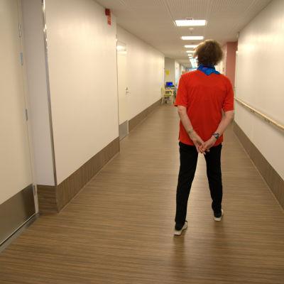 Iäkäs nainen seisoo käytävällä.