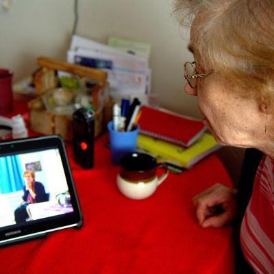 Iäkäs nainen katsoo tablettitietokoneelta videota.