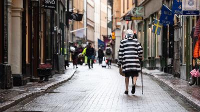 En kvinna går på en gata i Gamla stan i Stockholm.