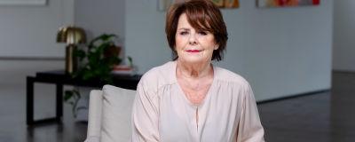 Pirkko sitter med slutna händer i en vit fåtölj. Hon ser rakt in i kameran och i bakgrunden syns färggranna tavlor på väggen.