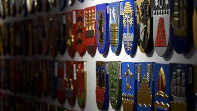 Två rader av kommunvapen i olika färger hänger på en vägg. De går mot mörker i slutet av väggen.