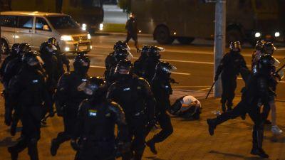 Kravallpoliser springer förbi en man som ligger hopkrupen på gatan