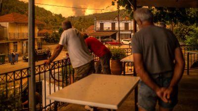 Tre män står på en balkong och tittar på en skogsbrand i bakgrunden.