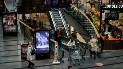 Rulltrappor med folk i köpcentrum.