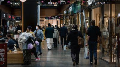 Mycket människor på rad i köpcentrum.
