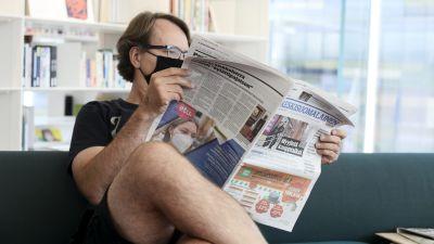 En man sitter och läser tidningen i Oodi. Han bär munskydd.