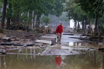 En man på en gata som inte längre finns för den är täckt av vatten och bråte efter översvämningen.
