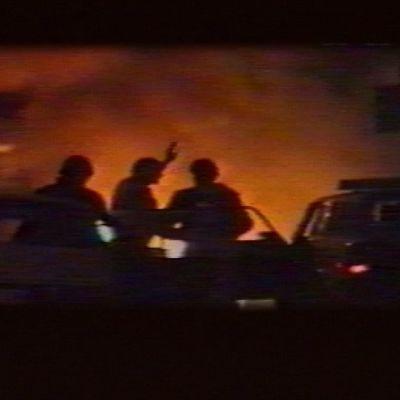 Autoja ja ihmisiä tulimeren edessä.
