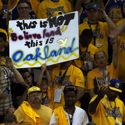 """Golden State-supportrar med en skylt. """"This is NOT believeland, this is Oakland""""."""