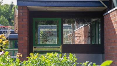 Klotter på fönstret vid en ingång till skolan.