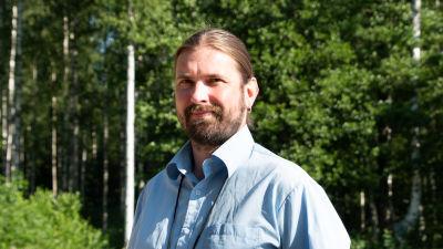 Kristian Meurman i ljusblå skjorta i solsken med lövträd i bakgrunden.