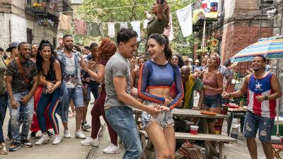 Usnavi (Anthony Ramos) och Vanessa (Melissa Barrera) dansar tillsammans omringade av en massa människor.