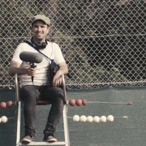 Nuori mies tenniskentän reunalla mikrofonin kanssa.