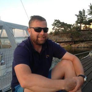 ung man sitter på brygga med bastu bakom och segelbåt bredvid sig