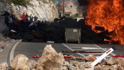 På söndagen hade demonstranterna tänt eld på sina barrikader för att se till att ingen kunde passera dem på väg mot klostret.