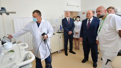 Rysslands premiärminister Michail Misjustin (andra från höger) och Moskvas borgmästare Sergej Sobjanin besöker att sjukhus utanför Moskva den 18 juni 2021.