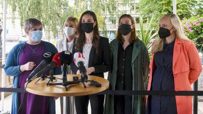 Annika Saarikko, Anna-Maja Henriksson, Sanna Marin, Li Andersson och Maria Ohisalo står framför ett talarpodium utanför Ständerhuset.