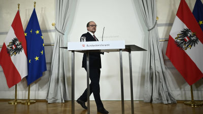 Mies kävelee puhujapaikalle, taustalla Itävallan ja EU:n liput
