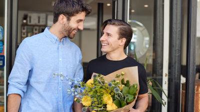 Två unga män ler mot varandra, den ena håller i en blombukett