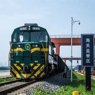Tavarajunan vihreä veturi raiteilla.