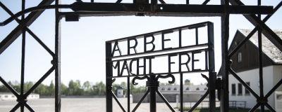 """Ståldörr till koncentrationslägret Dachau i Tyskland. På dörren står det """"arbetet befriar dig""""."""