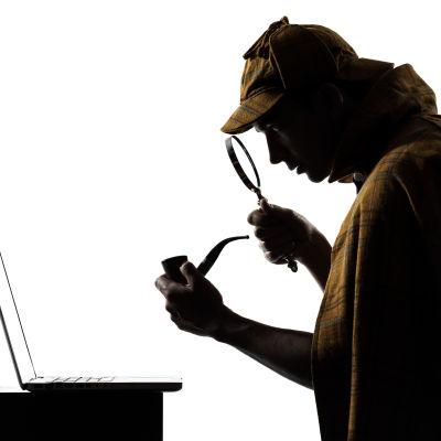Sherlock Holmes -hahmo katsoo suurennuslasilla kannettavaa tietokonetta