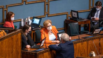 Antti RInne står med ryggen mot kameran och diskuterar med Sanna Marin och Tuula Haatainen i riksdagen under plenum 14.5.2021.