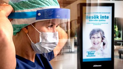 En sjuksköterska tar på sig skyddsutrustning - i bakgrunden ett köpcenter med en uppmaning att stanna hemma på en stor reklamskylt, text på svenska