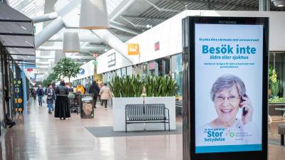 Coronainformation på en reklamskylt i ett köpcentrum.