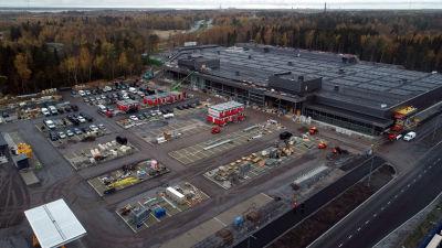 Affärscentret fotat från luften, stor parkeringsplats.