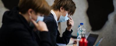 Abiturienter skriver preliminära studentprov med munskydd.