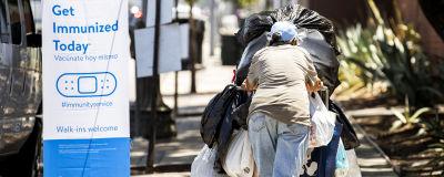 En person skuffar en köpkärra full av soppåsar med saker.