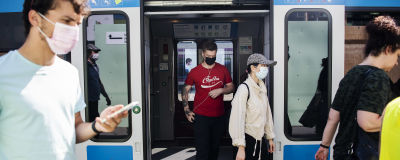 Människor i munskydd går ut från ett tåg i Helsingfors.