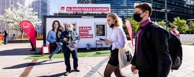 Socialdemokraternas valstuga i centrum av Helsingfors. Framför valstugan går en kvinna och en man med munskydd.
