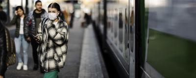 Kuvassa kasvomaskia käyttävä nainen astuu ulos junasta Helsingissä lokakuussa 2020.