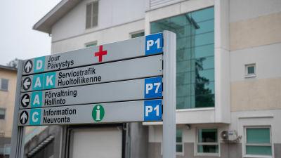 Ekenäs sjukhus sett från baksidan med en skylt i förgrunden