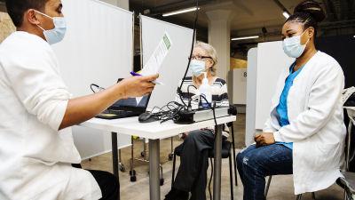 76-vuotias Maire Löppönen sai Astra Zenecan rokotteen, jonka pisti sairaanhoitaja Nguelah Elisè.