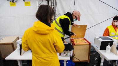 En kvinna förhandsröstar och håller på att lägga röstsedel i urnan.