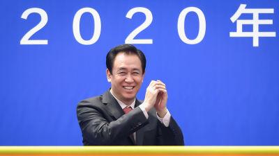 Affärsmannen Xu Jiayin iklädd kostym håller händerna i vädret. I bakgrunden siffrorna 2020.