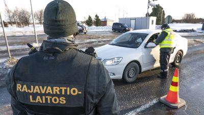 Två gränsbevakare checkar en personbil vid ett gränsövergångsställe.