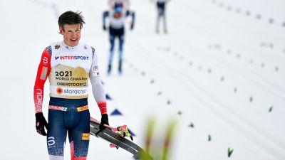 Johannes Høsflot Klæbo går med skidorna i vänsterhanden.