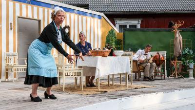 I framgrundern viftar rut och tittar ut mot publiken. Hon är klädd i gamla kläder som ett hembiträde kan tänkas använda. Bakom henne så sitter Regina och Agaton vid ett bord och tittar förundrande mot Rut.