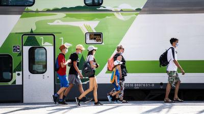 Människor i munskydd går på tågperrongen. I bild syns också ett av VR:s tåg.