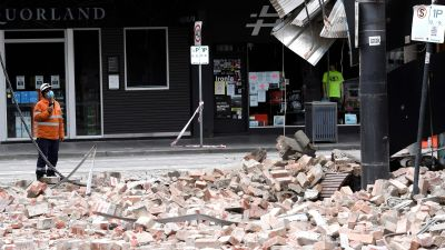 Räddningsarbetare inspekterar en rasad byggnad efter jordskalvet i Melbourne.