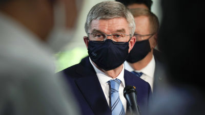 IOK:s ordförande Thomas Bach med munskydd, ser bekymrad ut