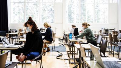 Studentskrivningar i ett gymnasium i Helsingfors i mars 2021. De studerande bär munskydd.