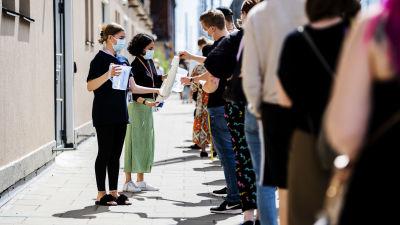 Emmi Sundén och Lura Aunimo delade ut vatten till personer som väntar i vaccinationskön. På bilden tar en ung man en pappmugg från en stor mugghögg som en kvinna håller i. En kvinna står bredvid med en vattenkanna i handen redo att fylla koppen.