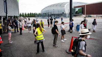 Människor står i kö till coronavaccinering vid Mässcentret i Helsingfors i juli 2021.