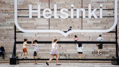 Människor står framför en Helsingforsskylt vid en trappa.