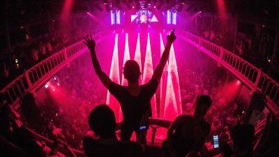 En person står på en balkong i en nattklubb och håller upp armarna. Nedanom honom ett hav med människor som dansar.